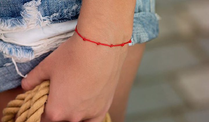 Красная нить на запястье: откуда она и зачем её носить?